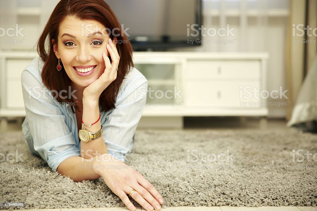 Smiling woman lying on the floor stock photo