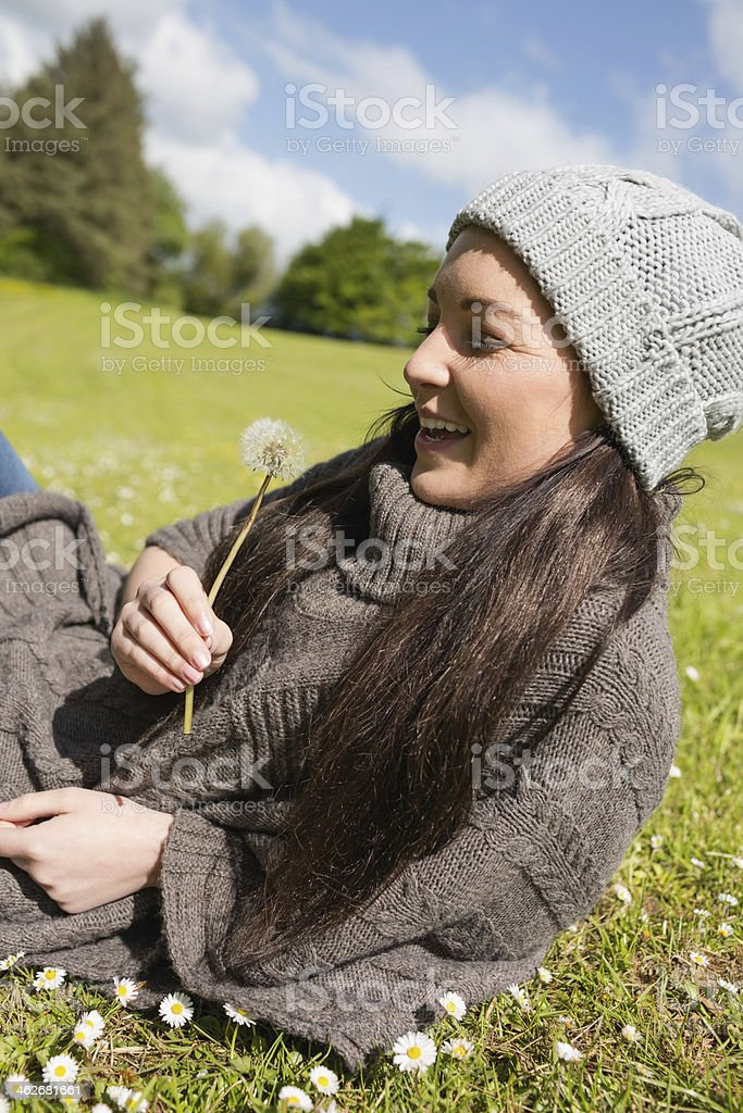 Smiling woman lying on the grass in green meadow royalty-free stock photo