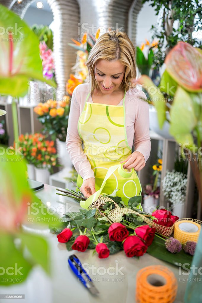 Smiling woman making rose bouquet in flower shop. stock photo