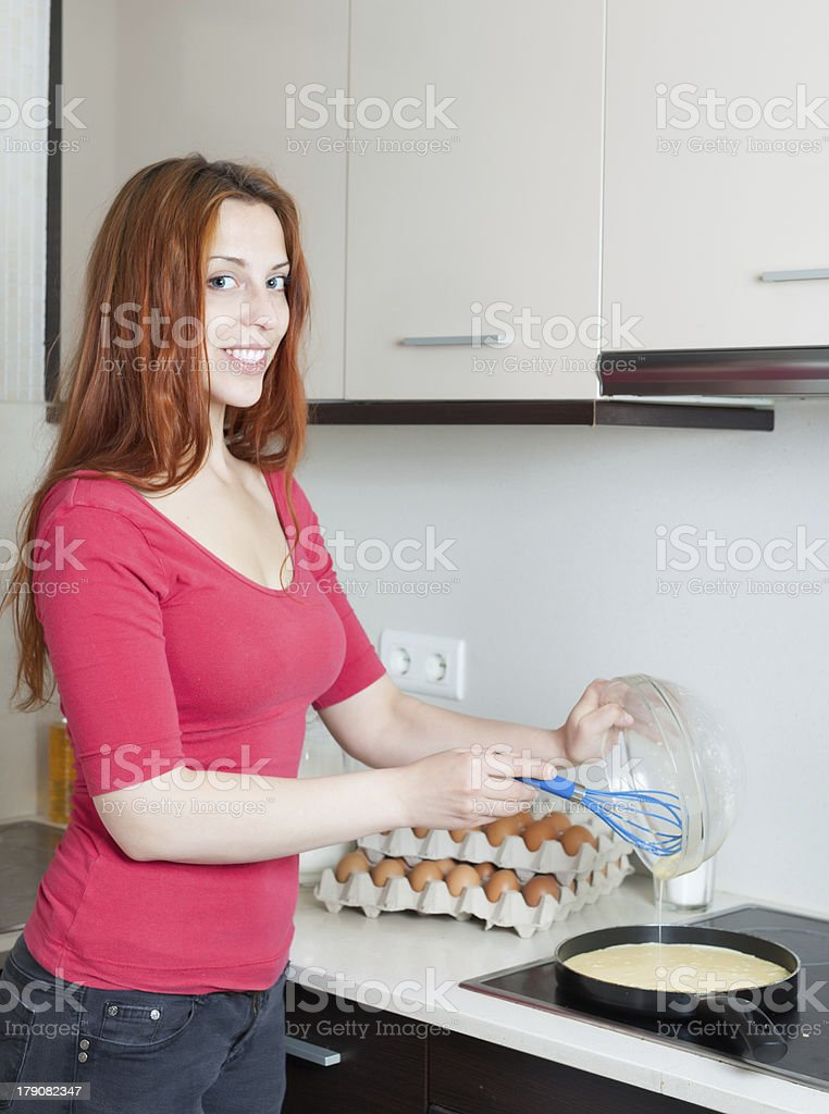 Smiling woman making scrambled eggs in frying pan royalty-free stock photo