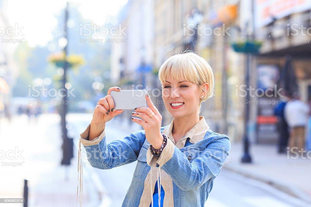 Smiling woman making selfie on street stock photo