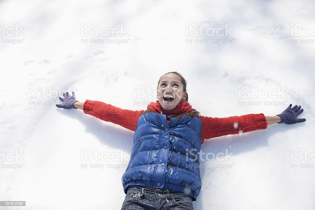 Smiling woman making snow angels royalty-free stock photo