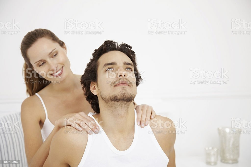 Smiling woman massaging a man's shoulders royalty-free stock photo
