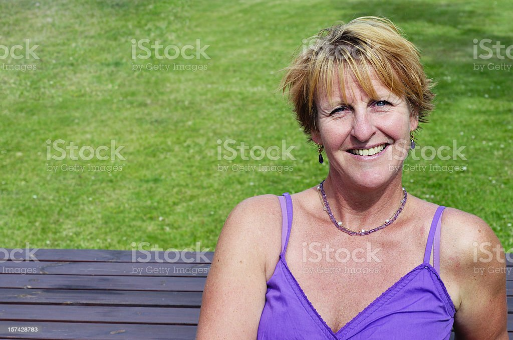 Smiling woman on a bench royalty-free stock photo