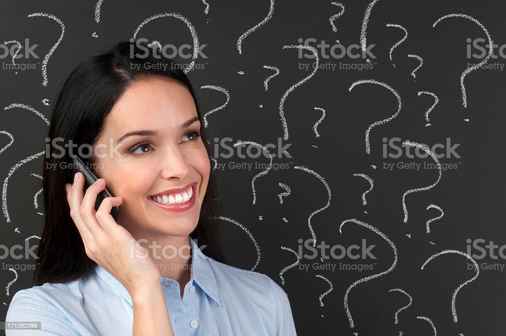 Smiling woman on cell phone in front of ??? on blackboard. royalty-free stock photo