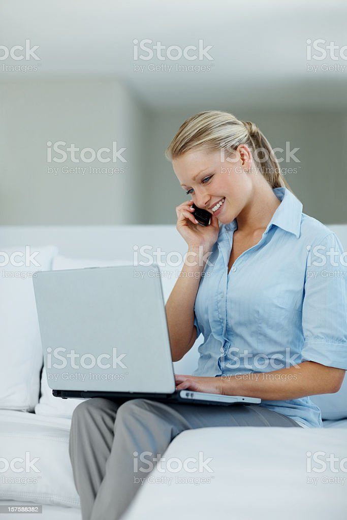 Smiling Woman on Couch With Laptop and Cell Phone royalty-free stock photo