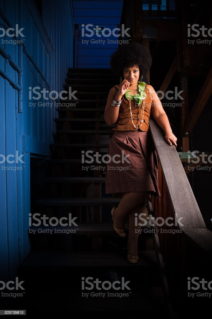 Smiling Woman on Shadowy Staircase stock photo