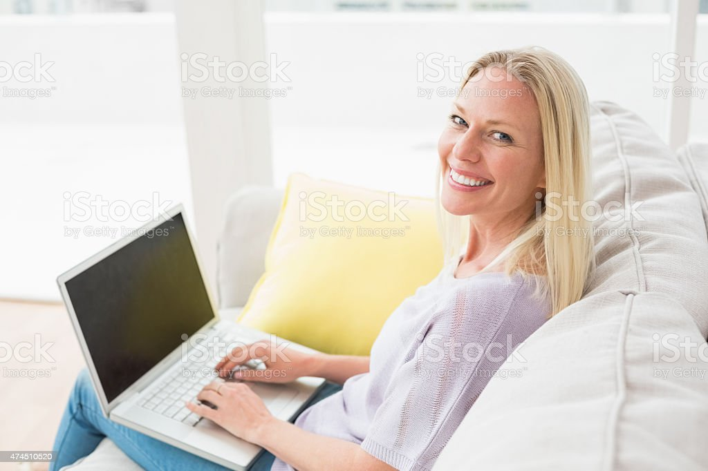 Smiling woman on sofa using laptop in living room stock photo