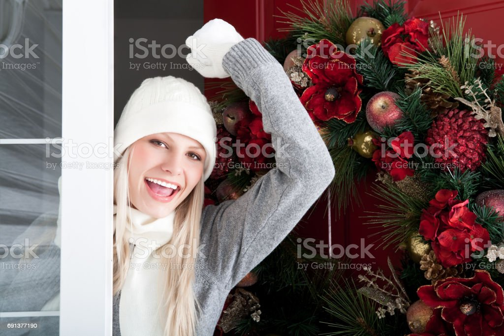Smiling woman opening front door with snowball stock photo