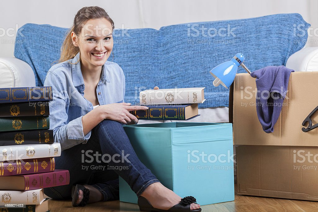 Smiling woman packing books stock photo