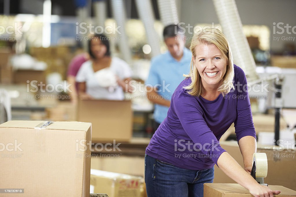 Smiling woman packing boxes for dispatch stock photo