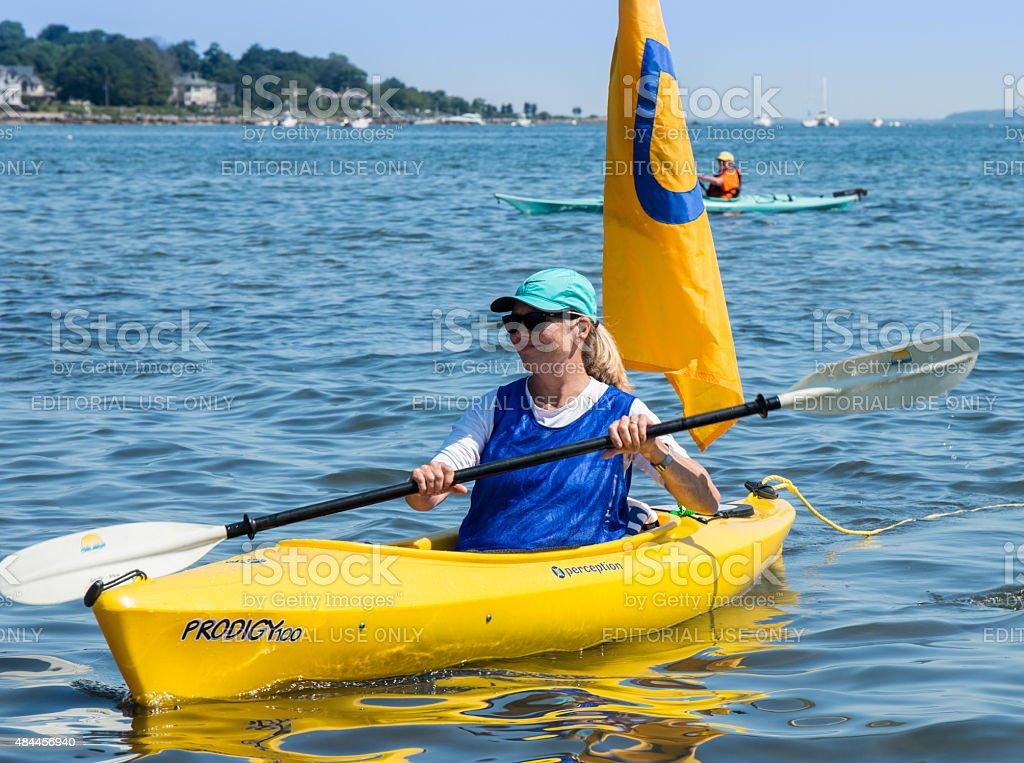 Smiling woman paddling a yellow ocean kayak stock photo