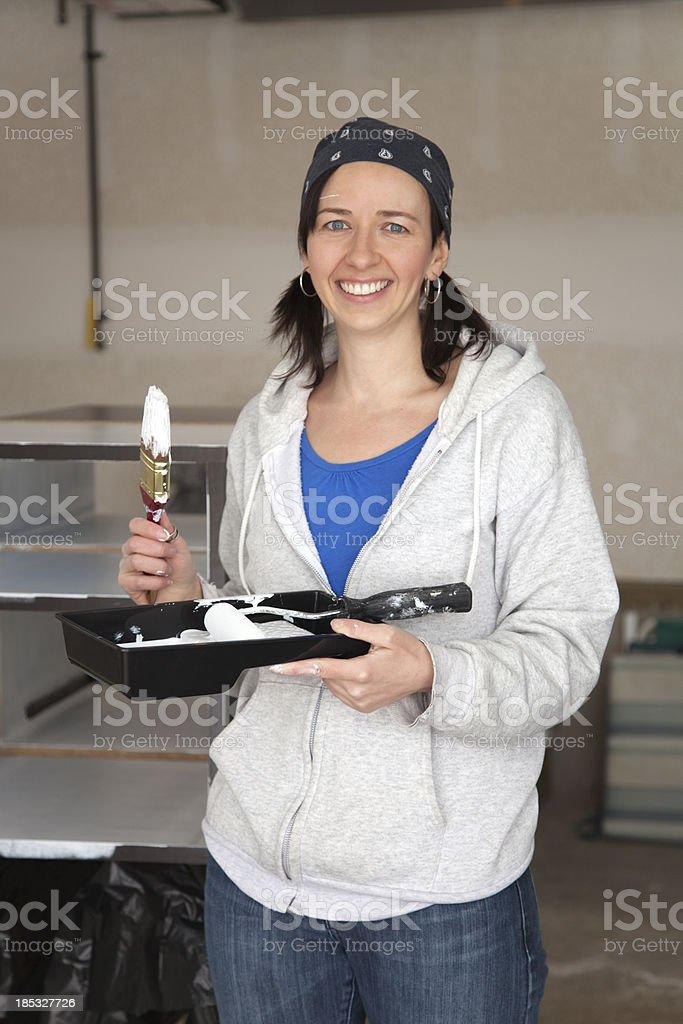 Smiling Woman Painting Shelves royalty-free stock photo
