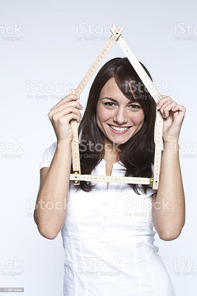 Smiling woman peering through a ruler shaped like a house stock photo