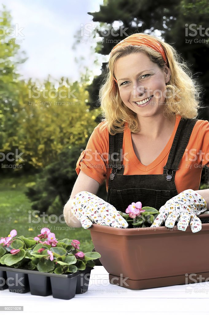 Smiling woman planting flowers in pots outdoors royalty-free stock photo
