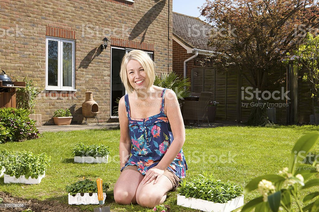Smiling woman planting trays of bedding plants in her garden royalty-free stock photo