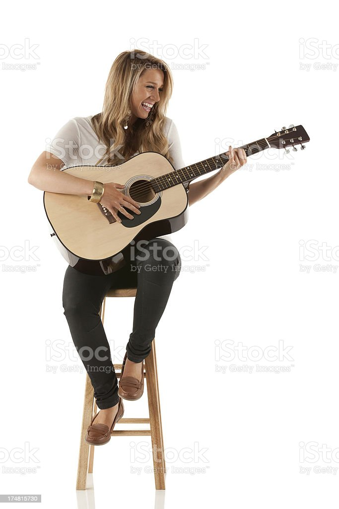 Smiling woman playing a guitar stock photo