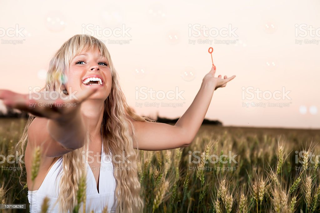 Smiling woman playing bubbles in wheat field royalty-free stock photo