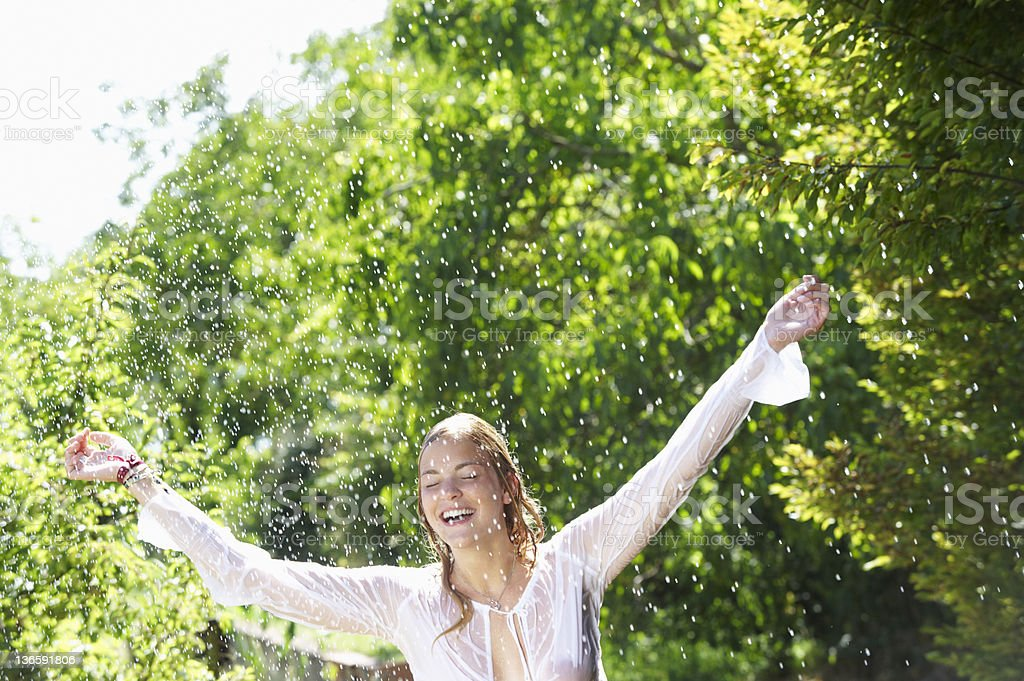 Smiling woman playing in rain shower royalty-free stock photo
