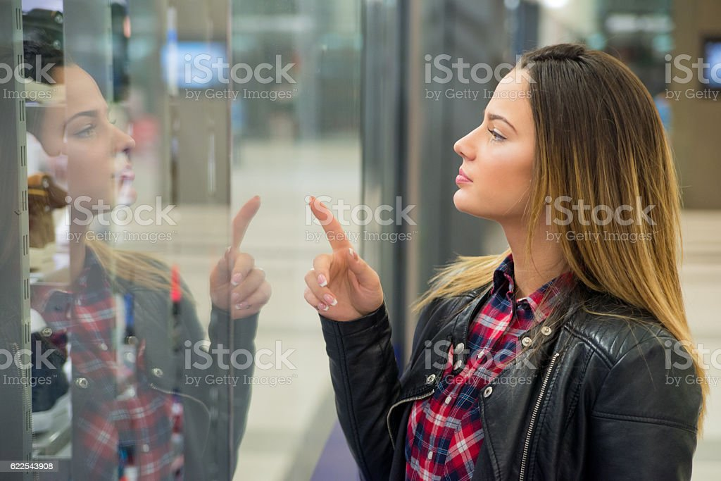 Smiling Woman  pointing the window at the shopping mall stock photo