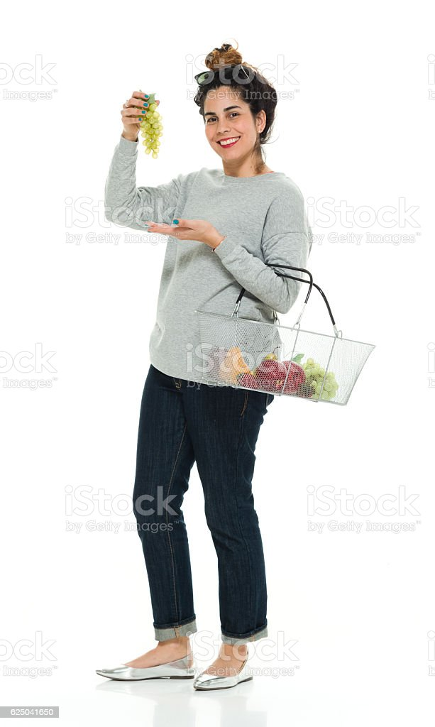 Smiling woman presenting with grape stock photo