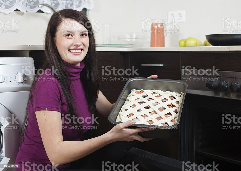 Smiling woman putting fish pie on roasting pan into oven stock photo