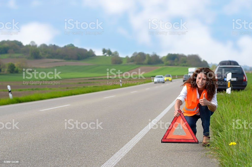 Smiling woman putting out a traffic warning sign stock photo