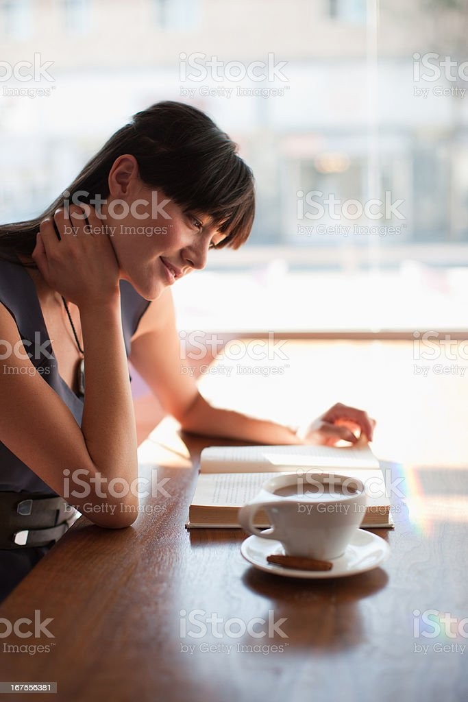 Smiling woman reading in cafe stock photo