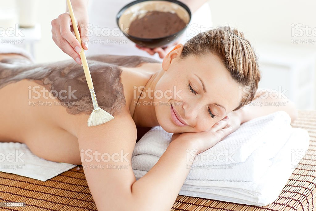 Smiling woman receiving mud skin treatment at a spa royalty-free stock photo