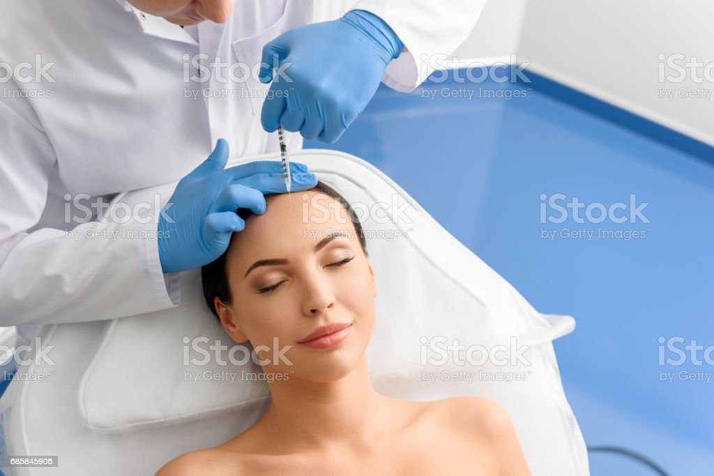 Smiling woman receiving treatments in beauty salon stock photo