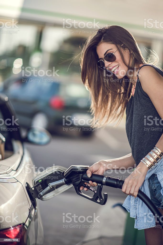 Smiling woman refueling her gas tank at fuel pump. stock photo