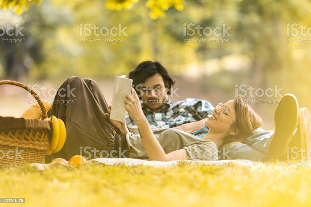 Smiling woman relaxing at picnic with boyfriend and reading book. stock photo