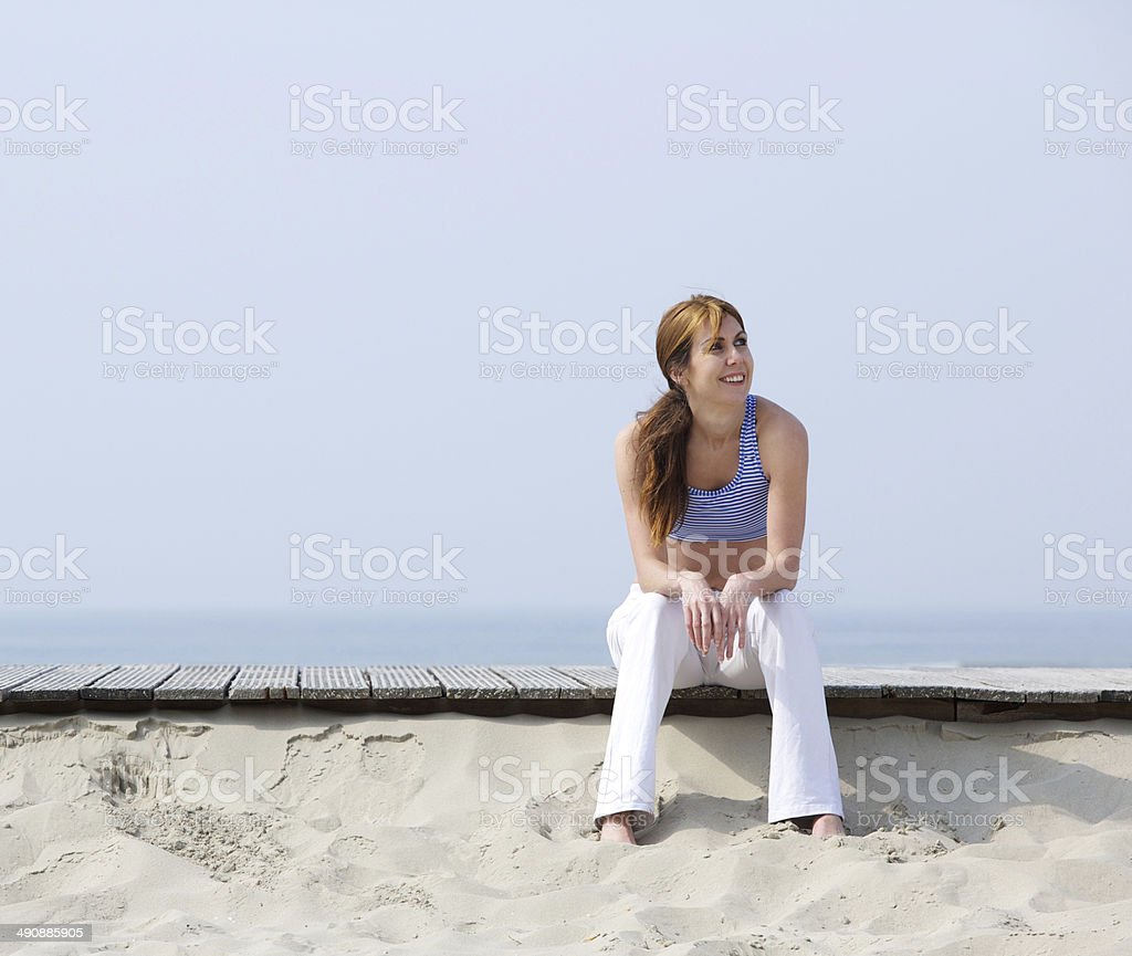 Smiling woman relaxing at the beach royalty-free stock photo