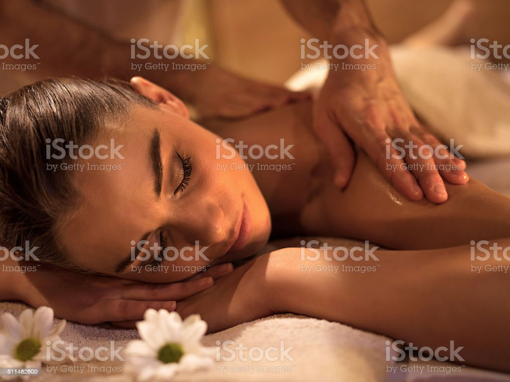 Smiling woman relaxing during back massage at spa. stock photo
