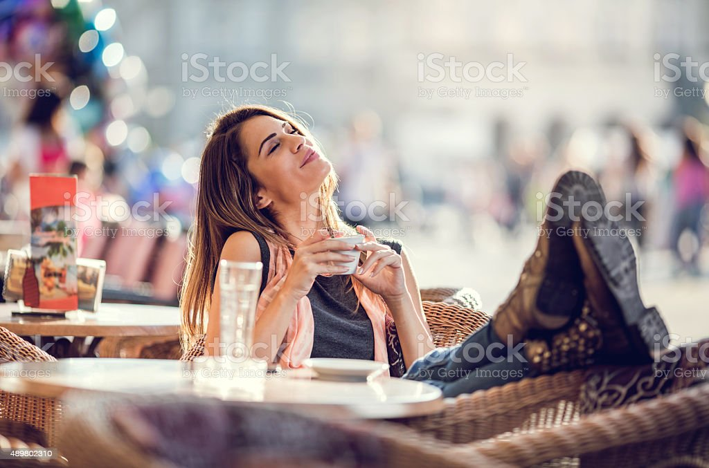 Smiling woman relaxing in a cafe with her eyes closed. stock photo