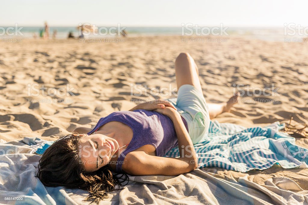 Smiling woman relaxing on beach towel stock photo