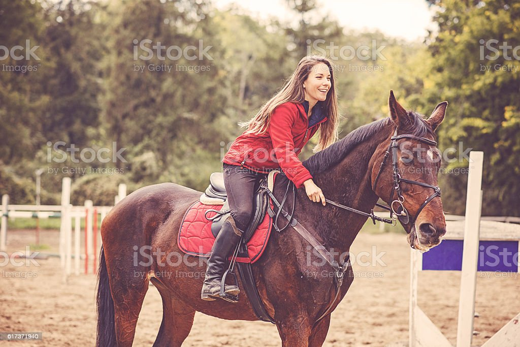 Smiling woman riding her horse on dressage stock photo