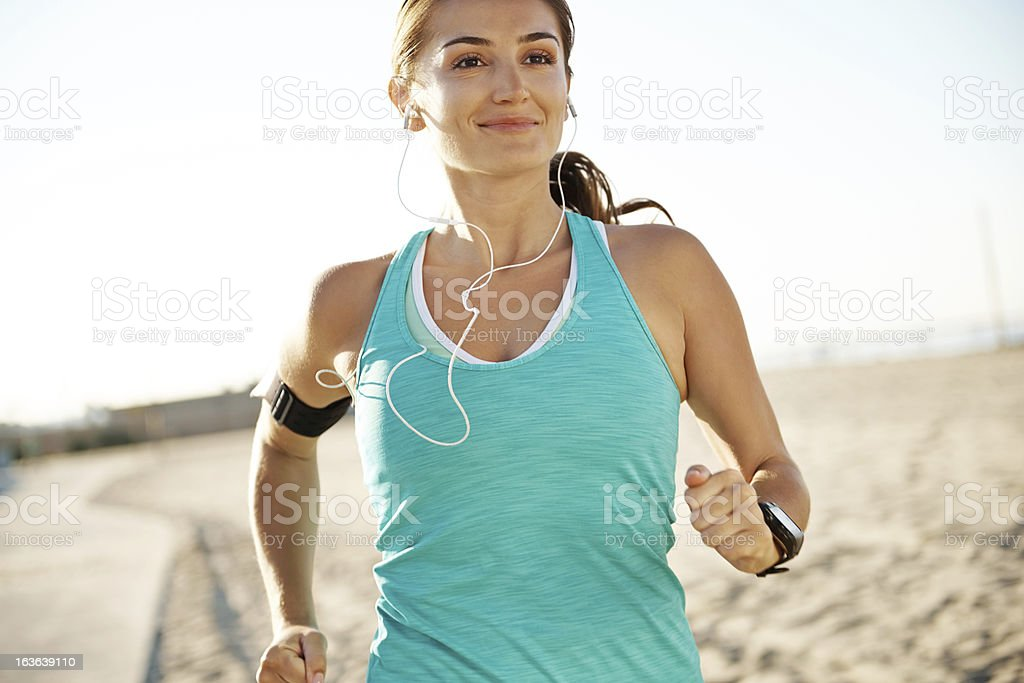 A smiling woman running while wearing earphones stock photo