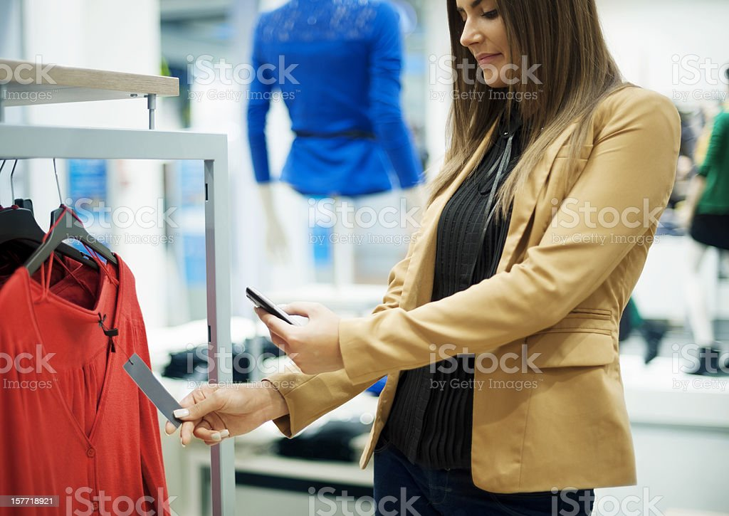 Smiling woman scanning QR code on smart phone stock photo