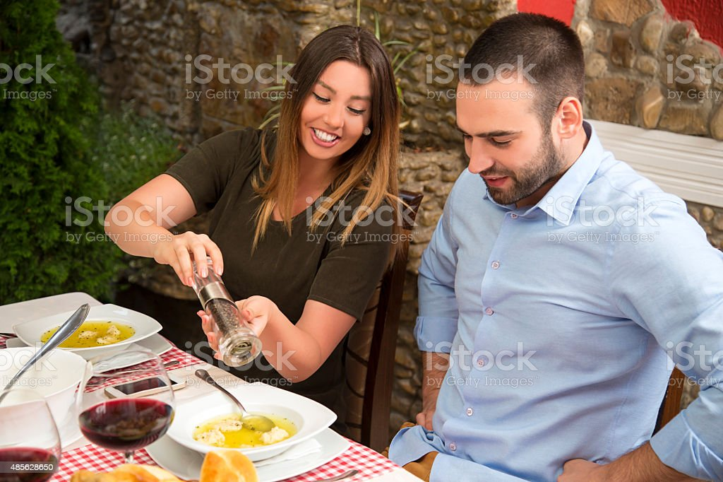 Smiling woman seasoning boyfriend's food in the restaurant. stock photo