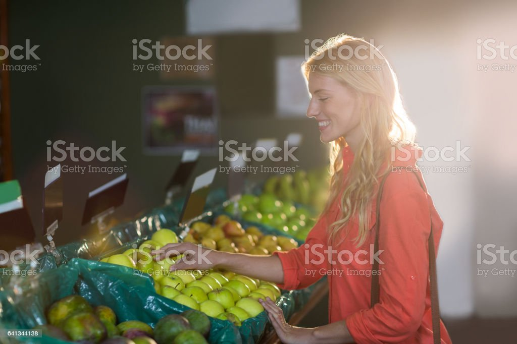 Smiling woman selecting green apples in organic section of supermarket stock photo