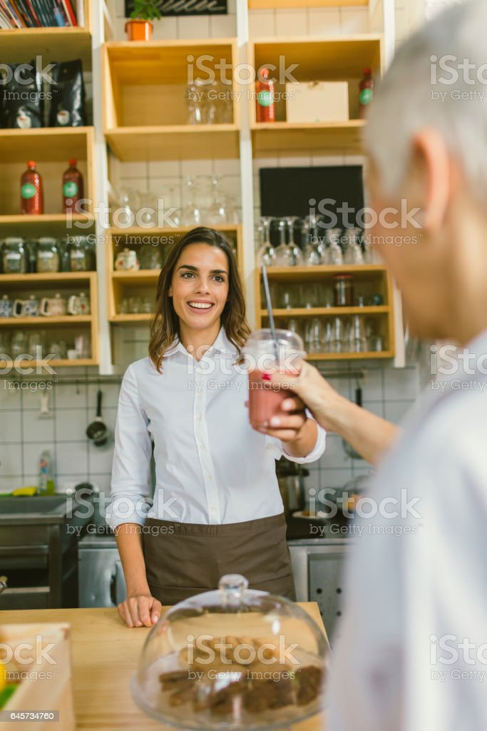 Smiling Woman serving smoothie to customer stock photo