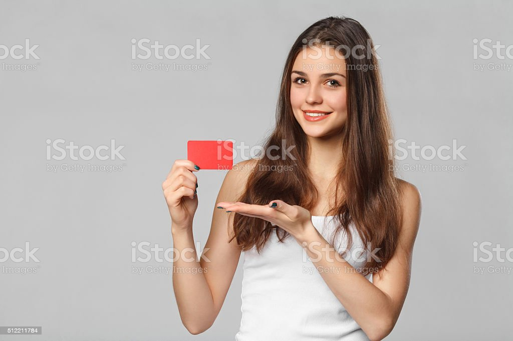 Smiling woman showing blank credit card in white t-shirt, isolated stock photo