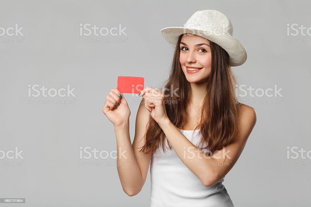 Smiling woman showing blank credit card, isolated over gray background stock photo