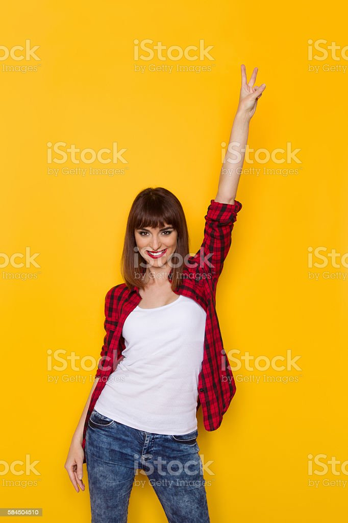 Smiling Woman Showing Victory Hand Sign stock photo