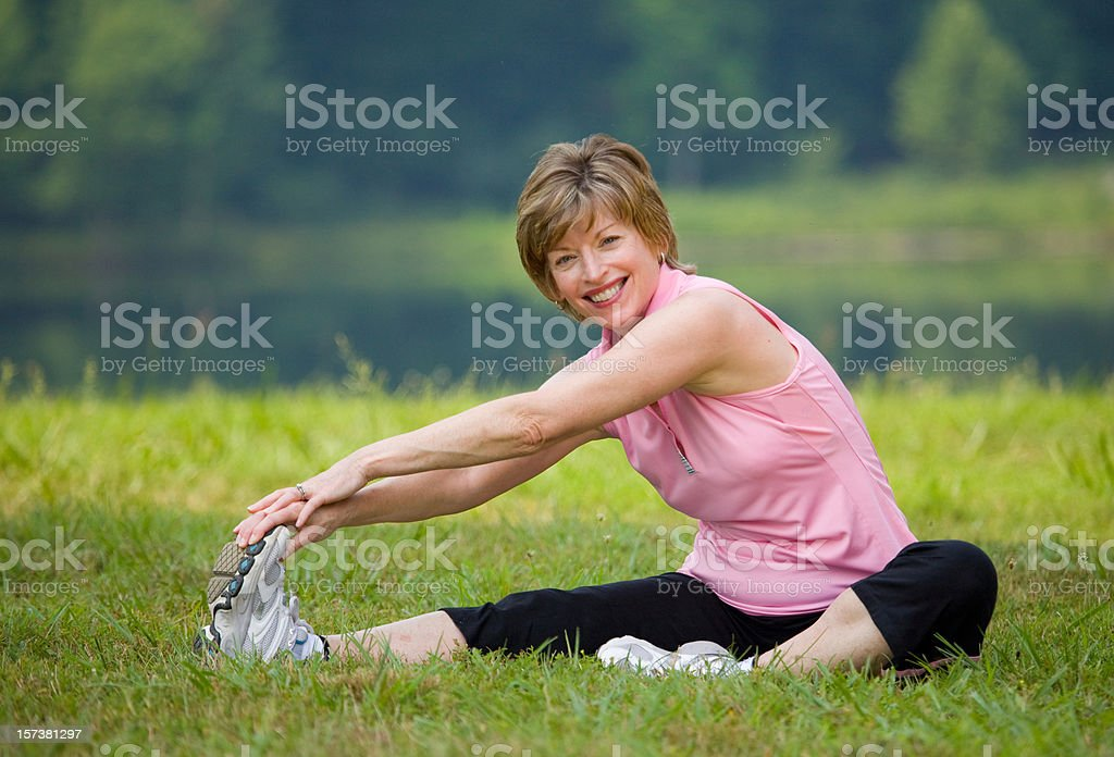 Smiling woman sitting and stretching over leg in the park royalty-free stock photo