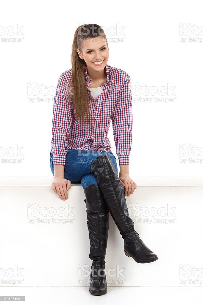 Smiling Woman Sitting At White Box stock photo
