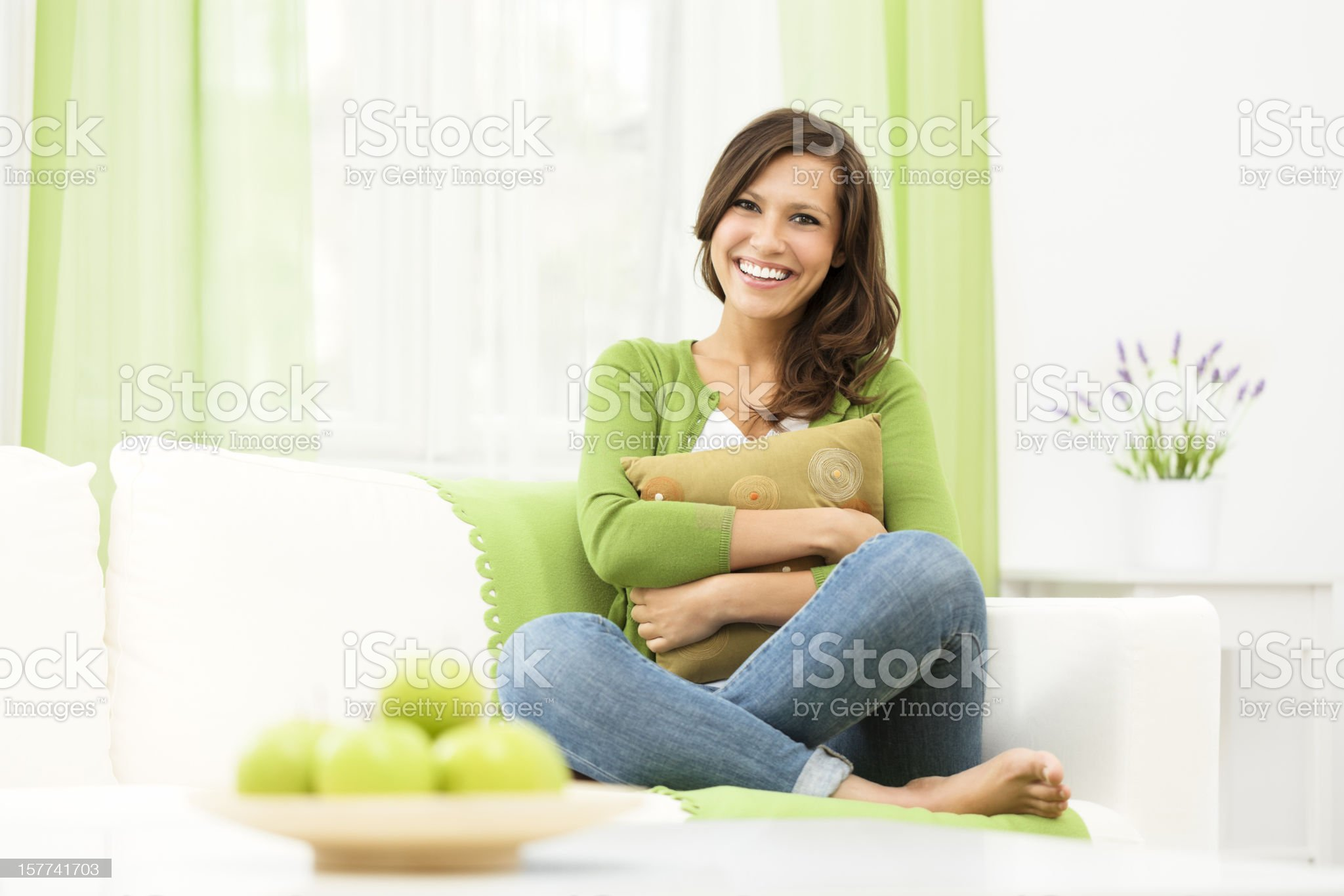 Smiling woman sitting confidently on a couch at home royalty-free stock photo