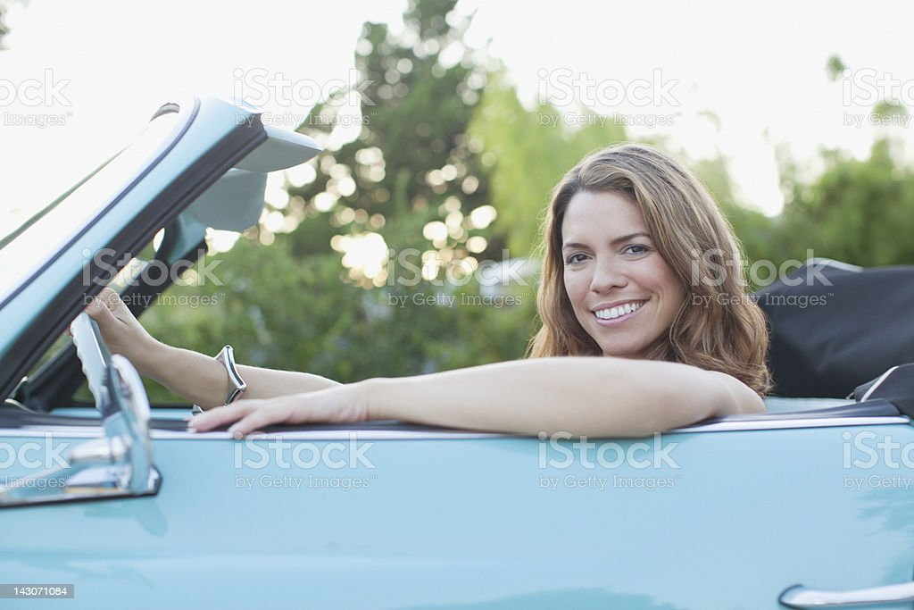Smiling woman sitting in convertible royalty-free stock photo