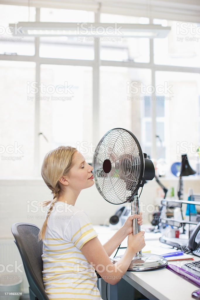 Smiling woman sitting in front of fan in office stock photo